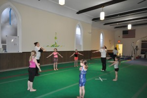 """Amy Garner, left, the owner of Gemini Gymnastics warms up with students at their location at 1288 Massachusetts Avenue in North Adams. Gillian Jones — The Berkshire Eagle"""